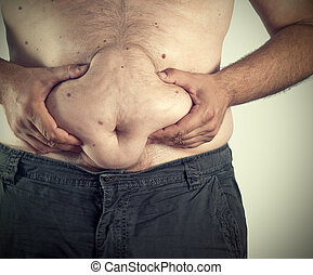 fat man - Close up of man grabbing his fat on the stomach