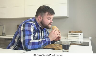 Fat man with a beard in a plaid shirt eats fast food...