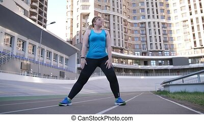 Fat positive woman during warm up on sports ground