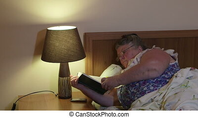 Fat senior woman reading book lying in bed at home