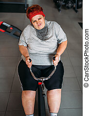 Fat sweaty woman, training on exercise machine