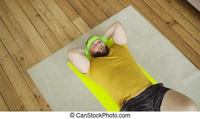 Fat tired man newcomer in sport wearing in yellow sportswear is doing abs exercise at home lying on mat, top view. Joke, mem, humor, parody. Workout, training, fitness, loosing weight concept.