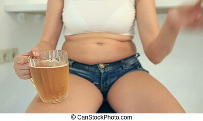 Fat woman drinking beer. A fat woman in a short T-shirt and shorts is drinking beer with chips in the beer bar. From under the vests are visible her folds of fat on her stomach