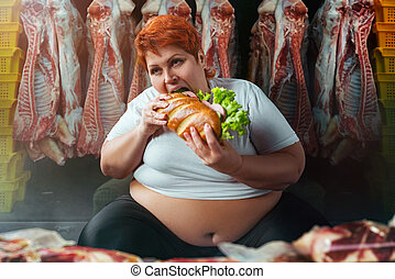 Fat woman eating burger against meat carcasses
