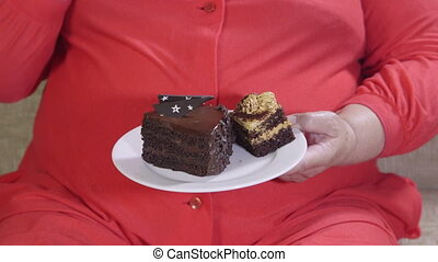 Overweight mature woman sitting on a couch and eating cake