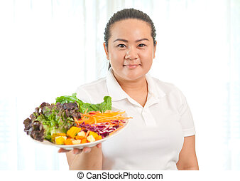 Fat woman eating salad