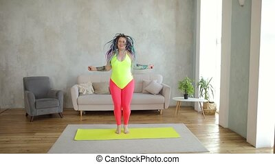 Fat woman in bright sportswear is jumping rope doing cardio at home, front view. Sport, fitness, training, workout, weight loss concept. Humor, mem, parody, fun behaviour. She has braided hairs.