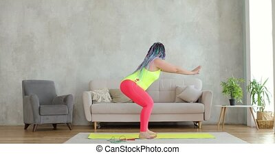 Fat woman in colourful sportswear with braided hairs is doing squats exercise training at home in living room, side view. Sport, workout, training concept. Joke, mem, fun behavior, fitness humor.