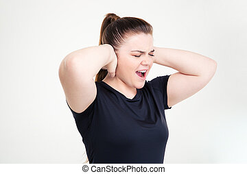 Fat woman in sportswear covering her ears and shouting -...
