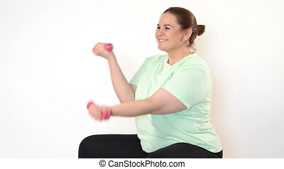 Fat woman making exercises with dumbbells isolated on white...