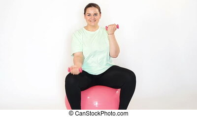 Fat woman making exercises with dumbbells on a fitness ball...