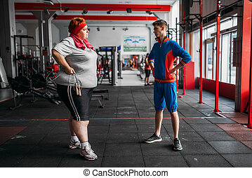 fat sweaty woman fitness exercise with rope in gym