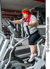 Fat woman using exercise machine for walking