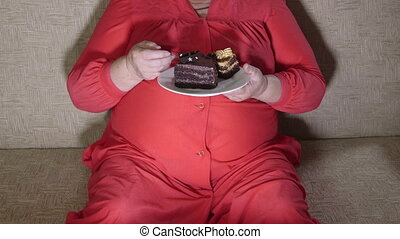 Fat woman watching television - Overweight mature woman...