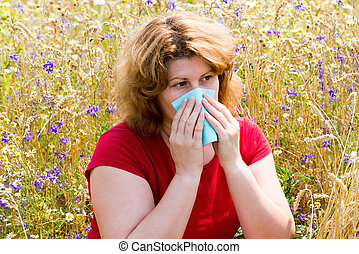 Fat woman with allergic rhinitis in the meadow