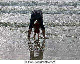 Father and a baby playing together in the sea