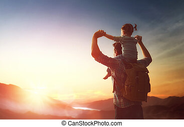 Happy family at sunset. Father and daughter are having fun and enjoying journey. Baby sits on the shoulders of his dad.