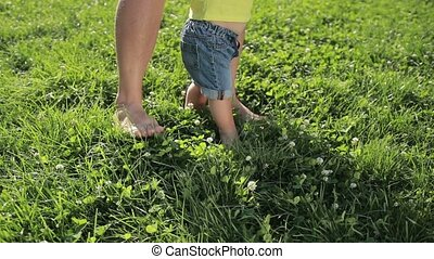 Father and baby boy feet walking barefoot on grass