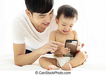 father and baby boy watching the mobile phone