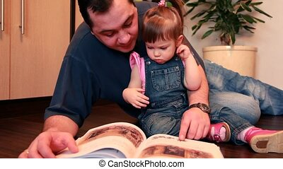 Father and baby girl are lying on the floor considering book