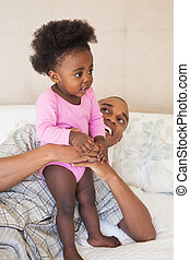 Father and baby girl lying on bed together