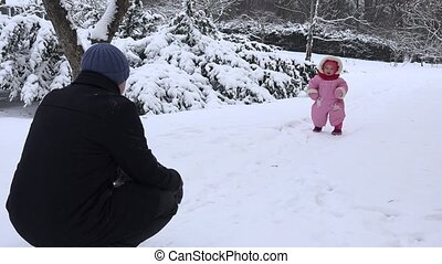 father and baby have fun in snowy park in cold winter time