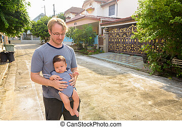 Father and baby son bonding together at home outdoors