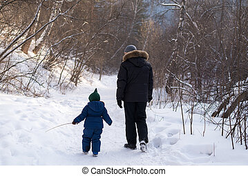 Father and child in a winter forest
