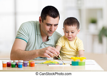 Father and child paint together. Dad teaches son how to paint correct and beautiful on paper. Family creativity and education at home.