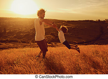 Father and child playing in nature at sunset.