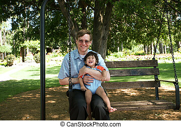 Father and child swinging