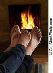Father And Child Warming Feet By Fire