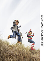 Father And Children Having Fun In Sand Dunes