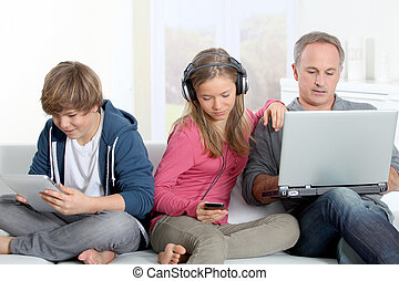 Father and children using electronic devices at home