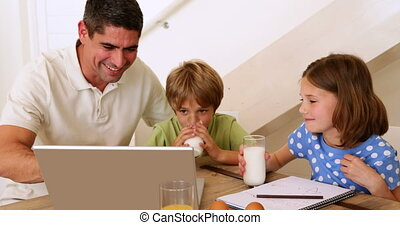 Father and children using laptop to