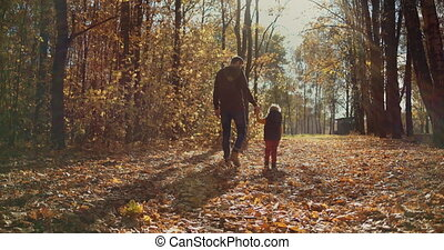 Father and children walking in the park and enjoying the beautiful autumn nature. Happy family on autumn walk. Slow motion. High quality 4k footage