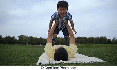 Father and cute asian son enjoiyng leisure outside