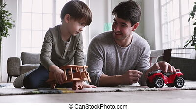 Father and cute small kid son playing funny racing game
