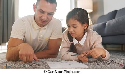 Father and daughter have fun and draw with crayons together. Concept of a happy family and quality leisure time