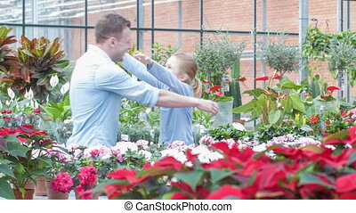 Father and daughter are hugging in the greenhouse.