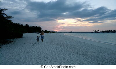 Father and daughter are on a beautiful white beach....