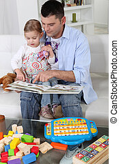 Father and daughter at home reading a book