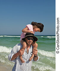 Young father and preschool daughter riding his shoulders, wading in the ocean surf. Ample copy space at top in the sky area.