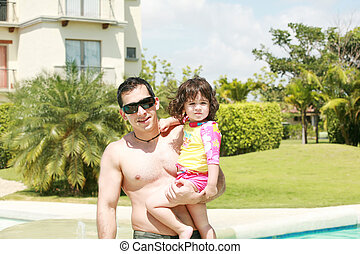 Father and daughter beside the swimming pool
