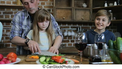 Father And Daughter Chopping Vegetables Cooking Together In Kitchen Talking With Son While Mother Using Tablet Digital Computer Happy Family Communicating At Home