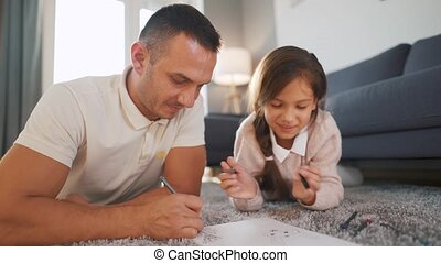 Father and daughter communicate, have fun and draw with crayons together. Concept of a happy family and quality leisure time