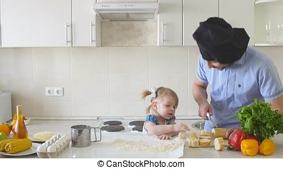 Father and daughter cooking at the kitchen.