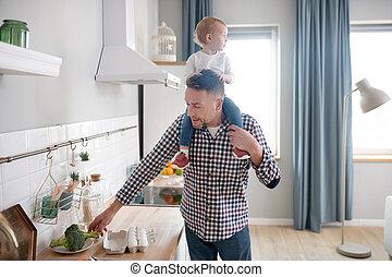 Cute little girl feeling great sitting on her fathers shoulders
