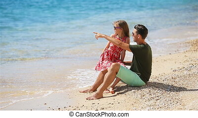 Father and daughter enjoy beach vacation - Young father with...