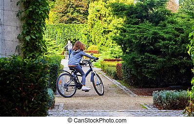 Father and daughter enjoy riding on bikes in park